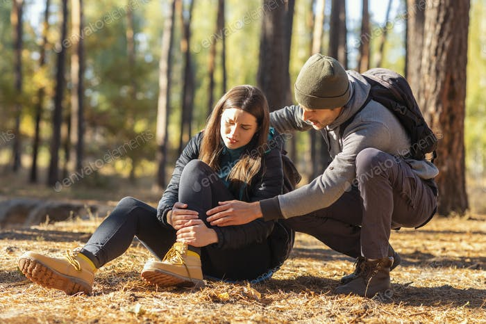 Young man rubbing his woman injured leg, hiking together