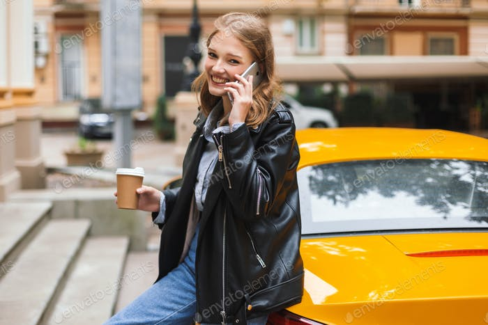 Beautiful smiling girl in leather jacket with cup of coffee to g