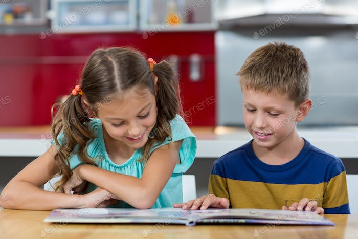 Smiling siblings looking at photo album in kitchen