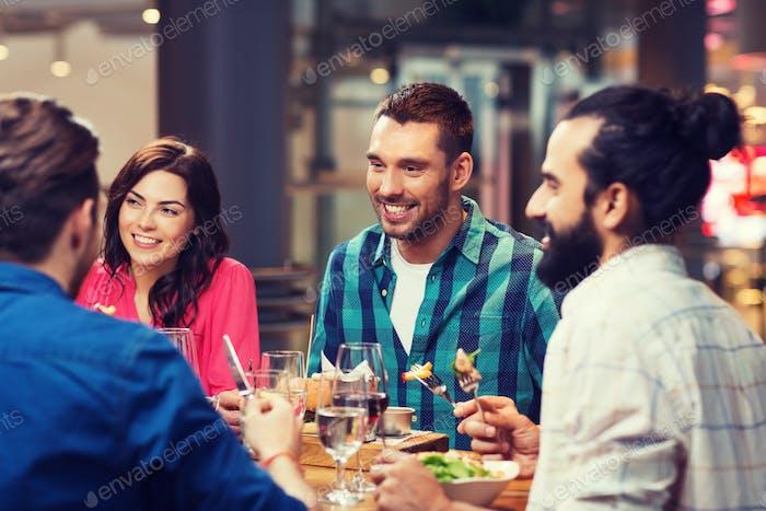 happy friends having dinner at restaurant