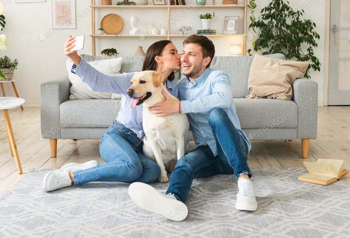 Young couple taking selfie with their dog in living room