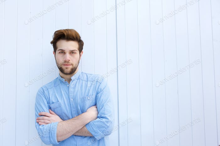 Serious young modern man standing with arms crossed