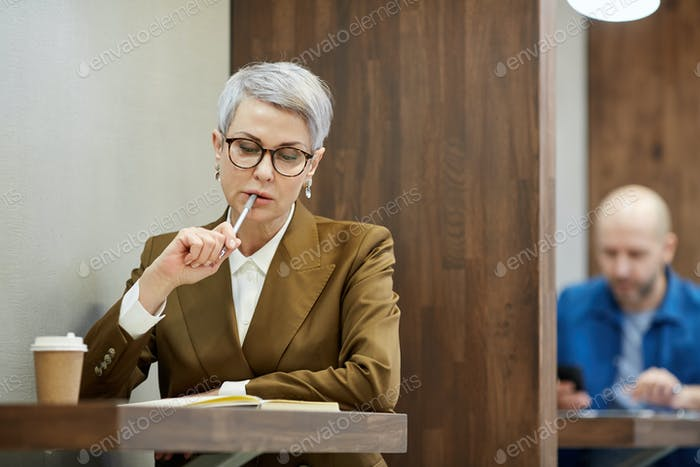 Pensive Mature Businesswoman Working in Cafe