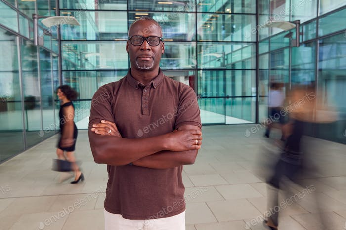 Portrait Of Mature Businessman With Crossed Arms Standing In Lobby Of Busy Modern Office