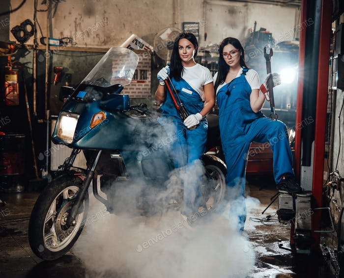 Thumbnail for Two female mechanic posing next to a sportbike in authentic workshop garage surrounded by smoke