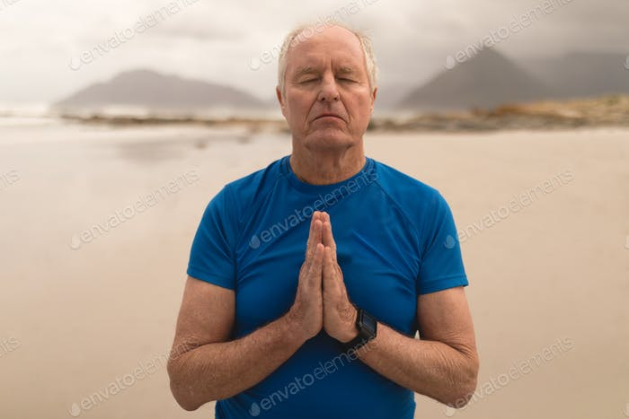 Front view of an active senior man meditating in prayer position on the beach