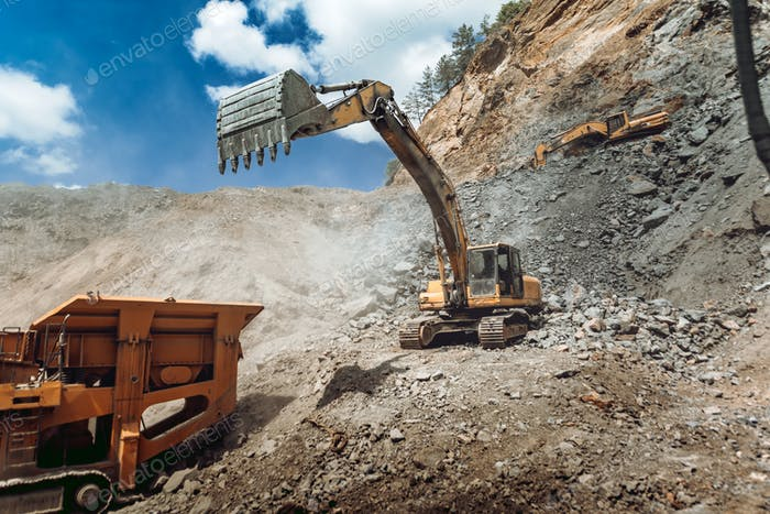 Track type excavator loading granite rock or ore quarry crushing and sorting plant
