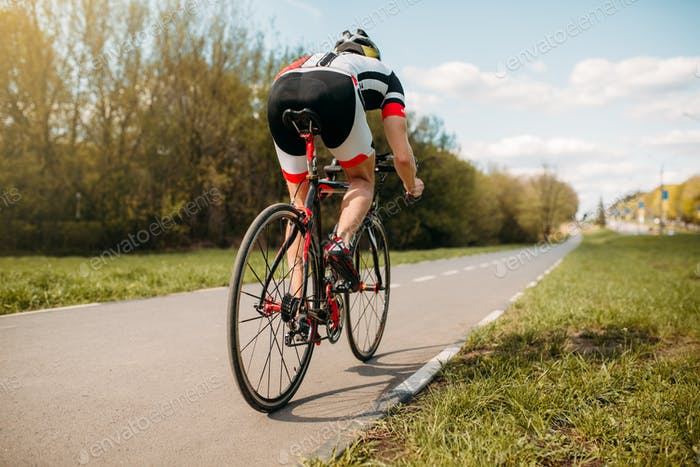 Cyclist rides on bicycle, side view