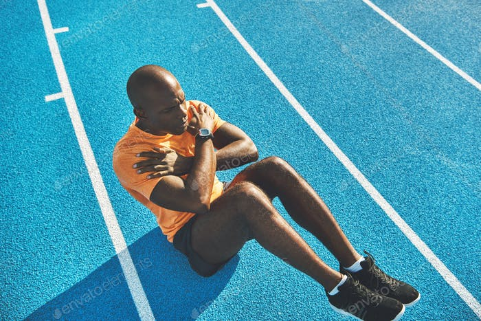Fit young athlete doing crunches on a track outside