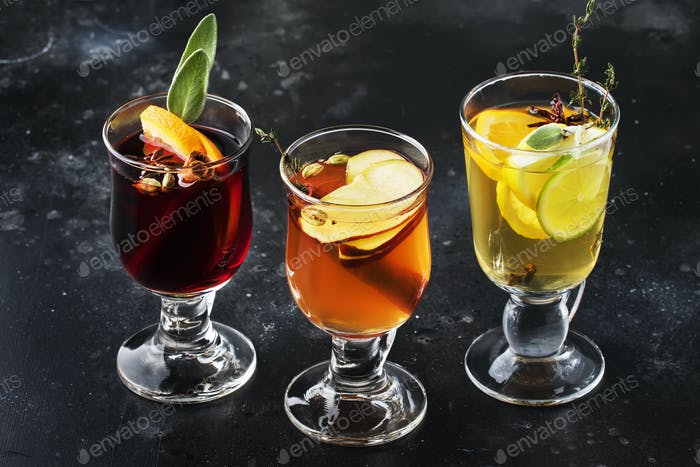 Mulled wine and mulled cider. Hot winter drinks and cocktails in glass mugs with spices
