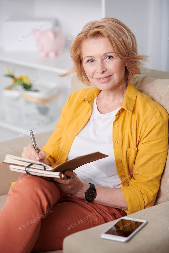 Successful businesswoman making working notes while sitting on couch at home