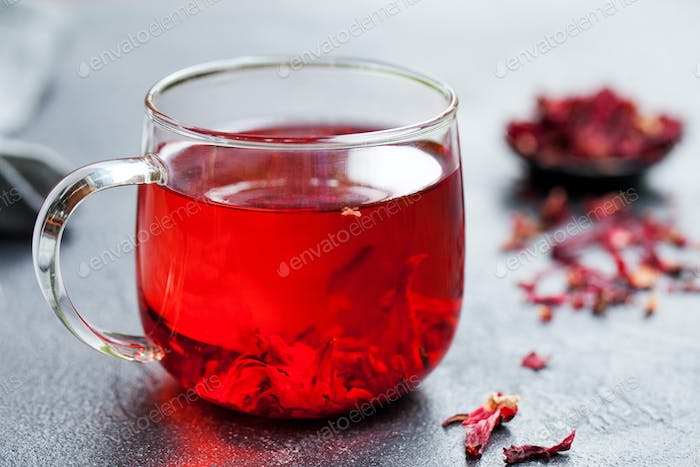 Hibiscus Tea in Glass Cup. Grey Background. Close up.