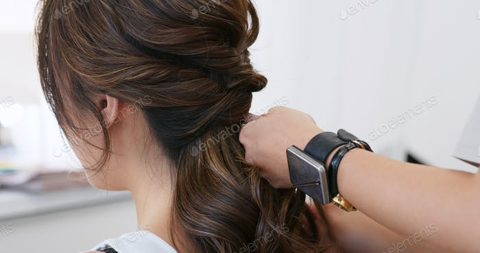 Hairdresser creating a hairstyle for bride in salon
