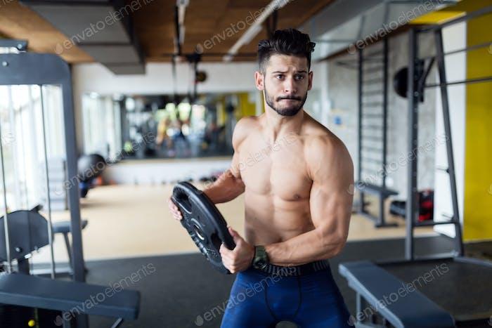 Porträt des jungen starken Mannes im Fitnessstudio