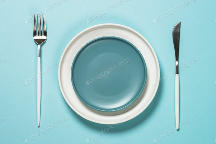 Table setting with white plate and cutlery on blue