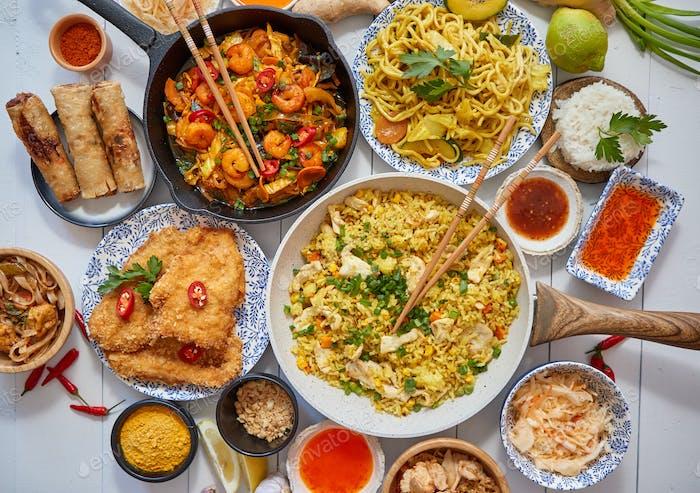 Asiatische Küche serviert. Teller, Pfannen und Schalen voller Nudeln Huhn rühren braten und Gemüse