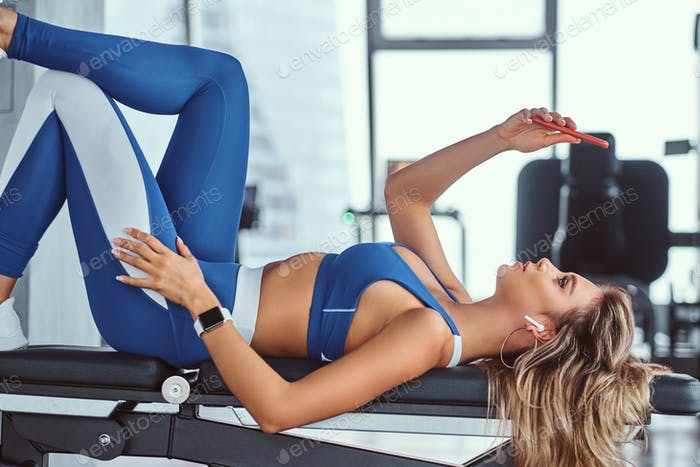 Beautiful fitness model lying on a bench in the gym.