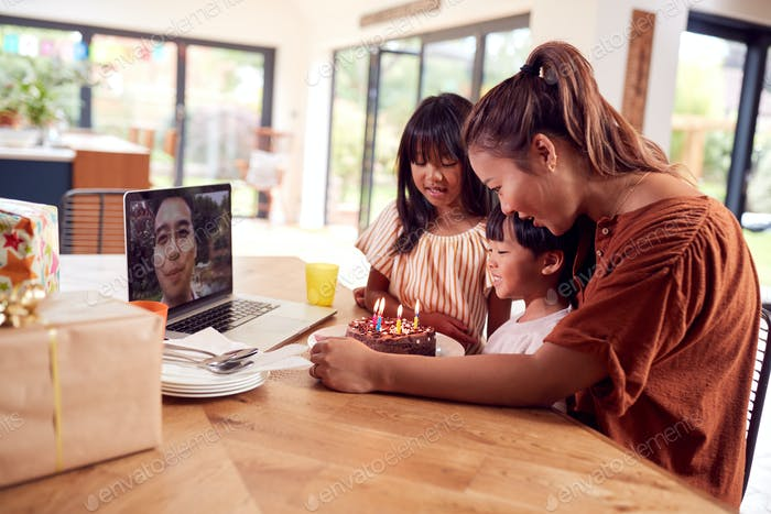 Asiatische Familie feiert Geburtstag zu Hause mit Vater, der per Video anruf wegarbeitet