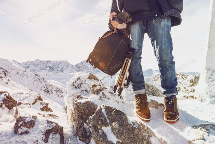 Photographer traveler on a mountain top with equipment in hands