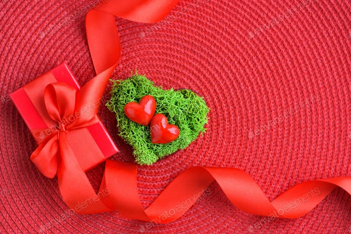 Valentines Day background. Hearts in green moss with red gift bo