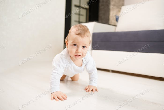 Baby boy crawling on his knees at home in living room.