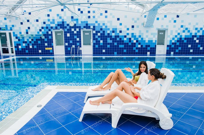 Two beautiful women are lying on chaise-longue poolside indoors and talking.