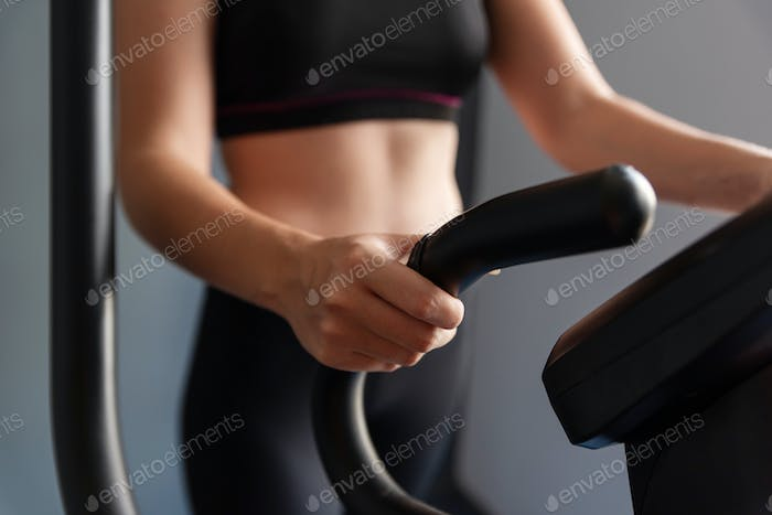 Woman Exercise Elliptical cardio running workout at fitness gym