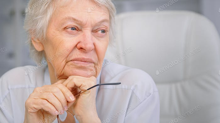 Thoughtful wise aged lady with sad eyes wrinkly face