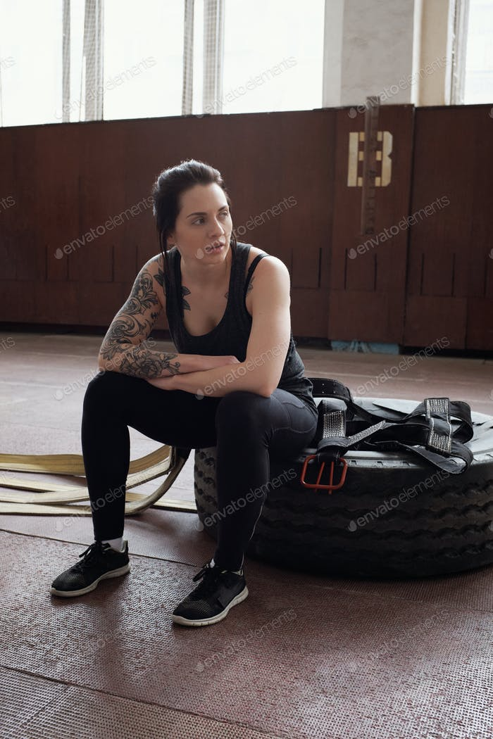 Young Caucasian female athlete with tattoos sitting on tire