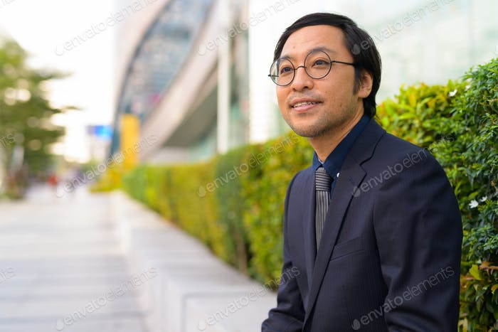 Happy Asian businessman thinking with nature in the city outdoors