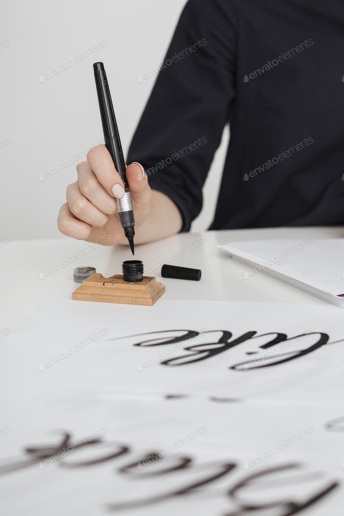 Close up photo of young woman hand writing on paper on desk  isolated