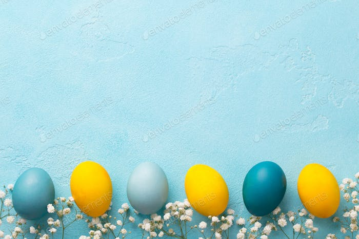 Colorful Easter Eggs with Flowers on Blue Background. Top View. Copy Space.