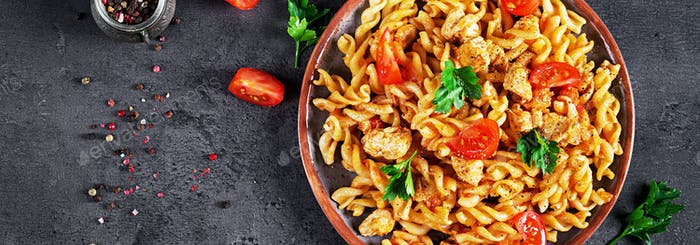 Pasta Fusilli  with tomatoes, chicken meat and parsley on plate
