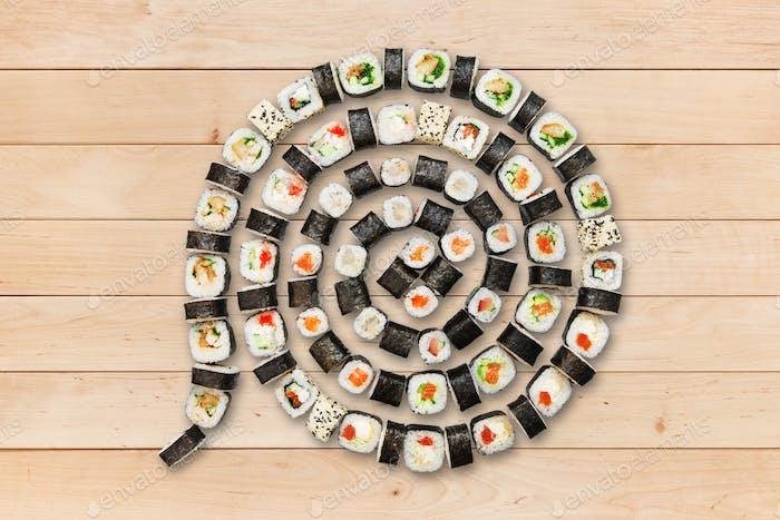 Set of maki sushi and rolls at wood.