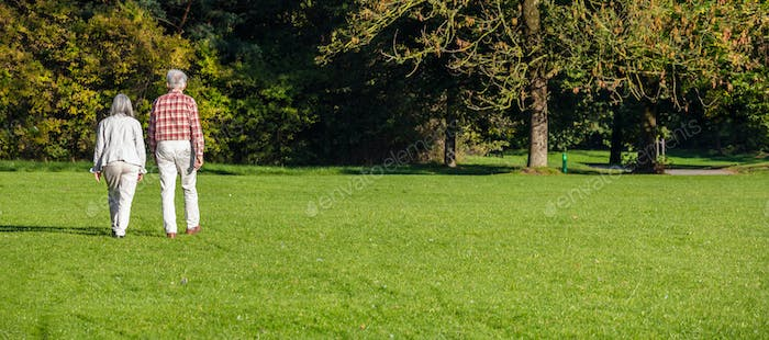 City park, Munich, Germany. View of a mature couple walking on the grass