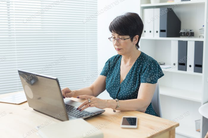 Business-, Technologie- und Menschenkonzept - Frau im mittleren Alter arbeiten im Büro und nutzen einen Laptop