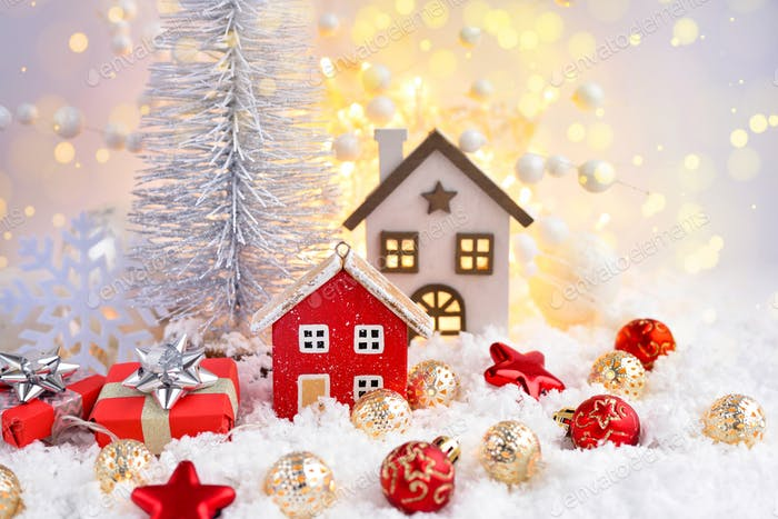 Christmas composition with decorative huts, gifts and festive decorations оn the snow
