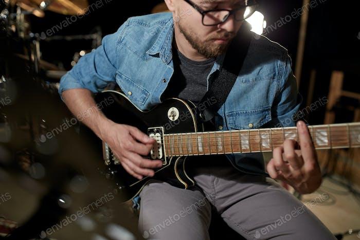 Mann spielt Gitarre bei Studioprobe