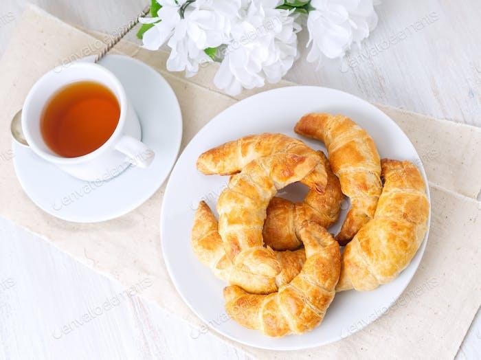 Tasse Tee, Blumen und frisch gebackenen Blätterteig auf einem weißen Tisch. Köstliche Croissants, Ansicht oben.