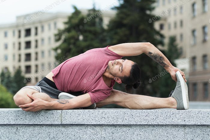 Man doing yoga stretching exercise in the city