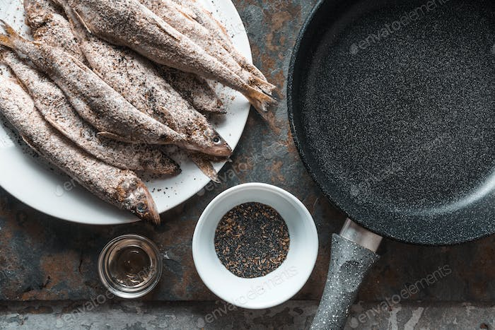 Smelt on a plate, frying pan, salt and spices