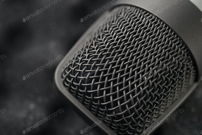 Gray studio condenser microphone on black soft foam of protective case. Macro shot