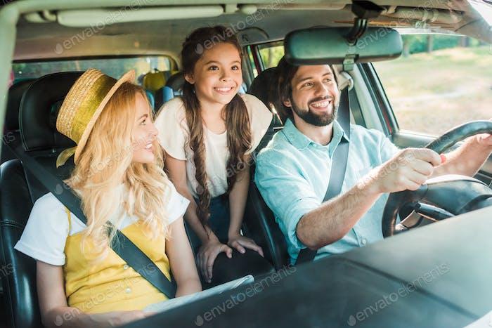 pais felizes e filha viajando de carro