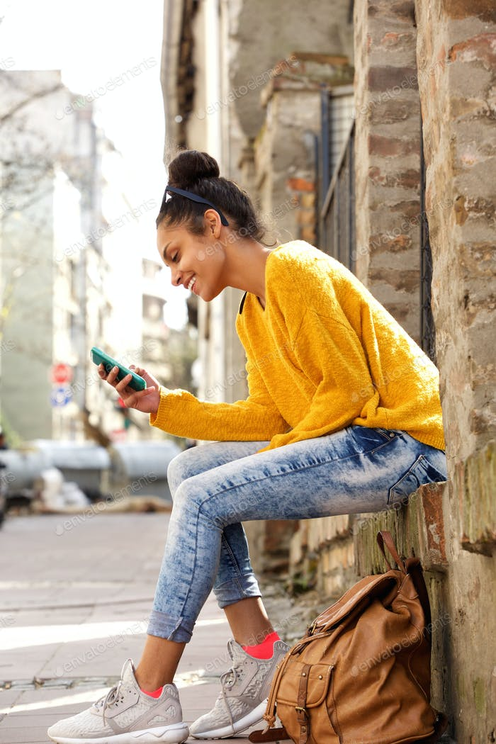 Happy woman sitting outdoors and using mobile phone