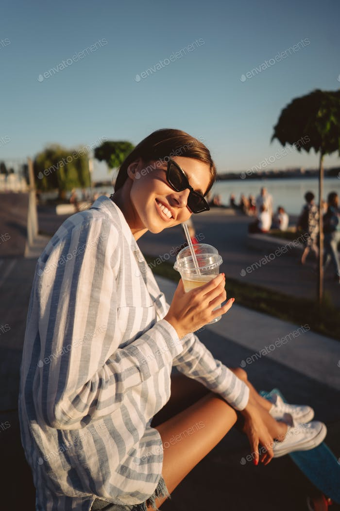 Young girl in sunglasses with a glass of lemonade