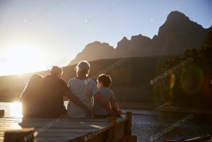 Grandchildren With Grandparents Sitting On Wooden Jetty By Lake