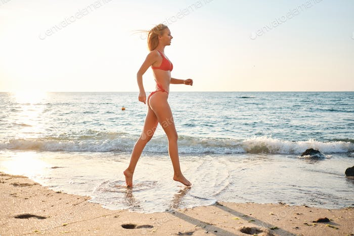 Gorgeous blond woman in swimsuit happily walking on sand with beautiful sunrise on background