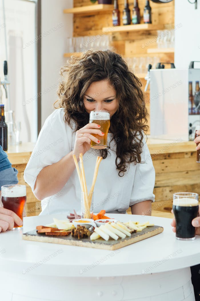 Smiling woman drinking craft beer