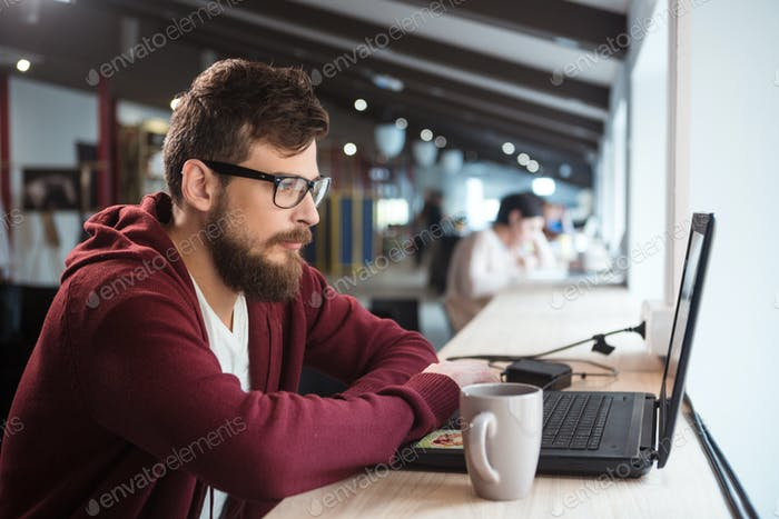 Young man in glasses sitting and using laptop