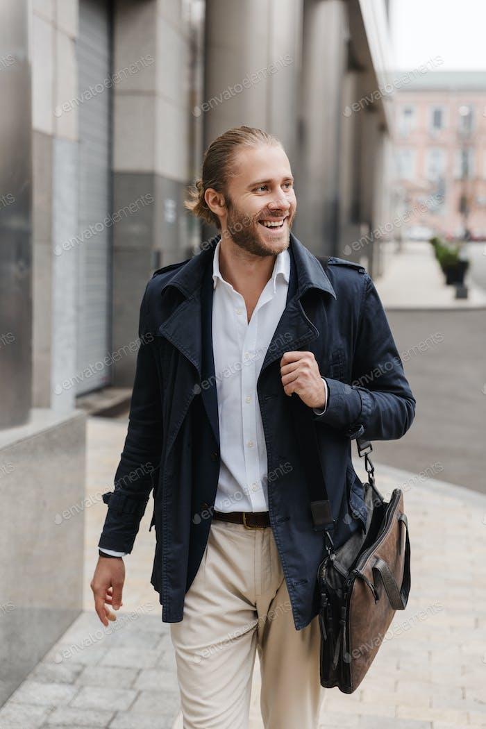 Attraktive junge bärtige Geschäftsmann zu Fuß im freien